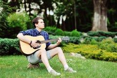 Ung stilig man med den utomhus- gitarren Fotografering för Bildbyråer