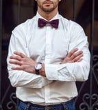 Ung stilig man med ett skägg i lyxig vit skjorta och blått omslag med bowtie Royaltyfria Bilder