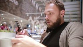 Ung stilig man med ett skägg som dricker kaffe eller te, genom att använda hans smartphone i ett kafé modern teknologi arkivfilmer