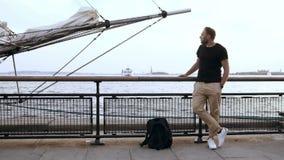 Ung stilig man med ryggsäckanseende på pir nära bogspröt för vatten nästan av skeppet och att se omkring stock video