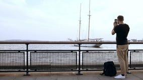 Ung stilig man med ryggsäckanseende på pir och tafotoet av det motoriska fartyget på smartphonen arkivfilmer