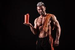 Ung stilig man med starka muskler, proteindrink efter trai Fotografering för Bildbyråer