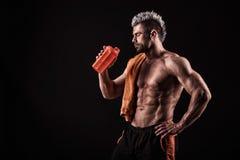 Ung stilig man med starka muskler, proteindrink efter trai Arkivfoton