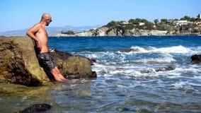 Ung stilig man på en stenig strand arkivfilmer