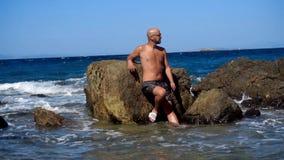 Ung stilig man på en stenig strand stock video