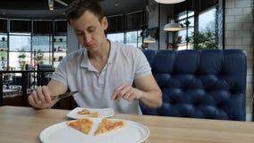 Ung stilig man som äter pizza på ett kafé arkivfilmer