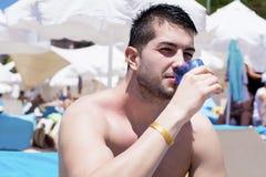 Ung stilig man som dricker kalla jin på stranden Arkivfoton