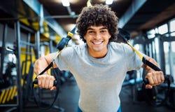 Ung stilig man som gör övningar i idrottshall fotografering för bildbyråer