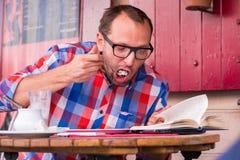 Ung stilig man som inomhus dricker kaffe i ett kafé och äter smörgåsen. Han golding en bok. Fotografering för Bildbyråer