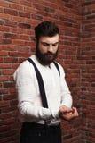 Ung stilig man som korrigerar skjortan över tegelstenbakgrund arkivfoton
