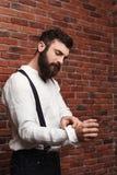 Ung stilig man som korrigerar skjortan över tegelstenbakgrund royaltyfri fotografi