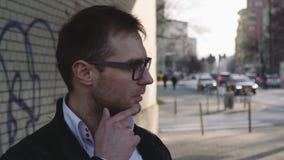 Ung stilig man som omkring ser i stadsgatan, borttappad riktning stock video