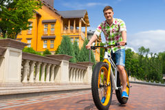 Ung stilig man som rider en färgrik gul cykel Royaltyfria Foton