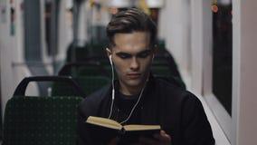 Ung stilig man som sitter på kollektivtrafik som läser en bok - pendlare, student, kunskapsbegrepp Ung man med arkivfilmer