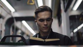 Ung stilig man som sitter på kollektivtrafik som läser en bok - pendlare, student, kunskapsbegrepp Ung man med stock video