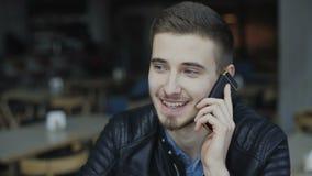 Ung stilig man som talar på smartphonen i kafét 4K stock video