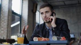 Ung stilig man som talar på smartphonen i kafét 4K arkivfilmer
