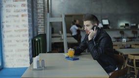 Ung stilig man som talar på smartphonen i kafét 4K lager videofilmer
