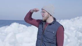 Ung stilig mangeolog som fokuseras på något nära kall is som snöar glaciären bak vinterhavet l?ngsam r?relse arkivfilmer
