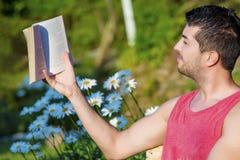 Ung stilig manläsebok i en grön blommande trädgård Royaltyfri Foto