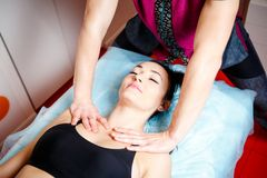 Ung stilig manlig massageterapeut som gör en avslappnande klassisk massage i en flickaugn som ligger på en massagetabell i en skö