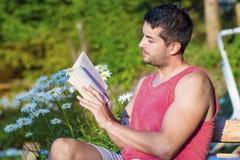 Ung stilig manläsebok i en grön blommande trädgård Royaltyfria Foton