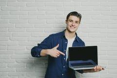 Ung stilig manpunkt fingret på en bärbar dator för tom skärm som ser kameran, lyckligt leende, mot en tegelstenvägg Arkivfoto