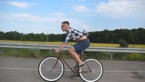 Ung stilig manridning på tappningcykeln i landsvägen Sportig grabb som cyklar på spåret Manlig cyklistridning lager videofilmer