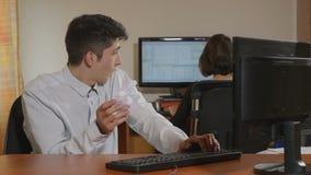 Ung stilig programmerare som kastar papper, klumpa ihop sig in i hans medarbetare lager videofilmer