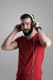 Ung stilig skäggig grabb som sätter på vit hörlurar arkivbild
