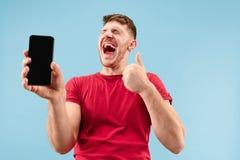 Ung stilig skärm för manvisningsmartphone som isoleras på blå bakgrund i chock med en överraskningframsida arkivbild