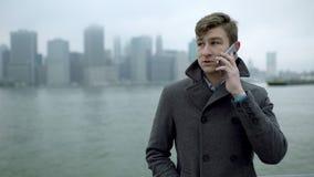 Ung stilig turist som talar över smartphonen nära Hudson River lager videofilmer