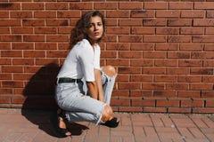 Ung storartad flicka med ljus-brunt lockigt hår i vita t-skjorta och grov bomullstvillflåsanden fotografering för bildbyråer