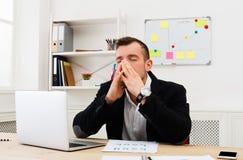 Ung stressad affärsman med bärbara datorn i modernt vitt kontor arkivbilder
