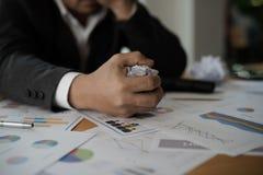 Ung stressad affärsmanhand som griper ett papper på hans skrivbord a Royaltyfria Bilder