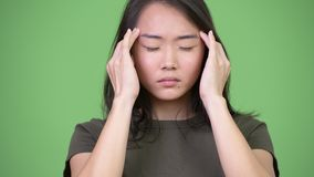 Ung stressad asiatisk kvinna som har huvudvärk arkivfilmer