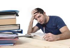 Ung stressad student som studerar på arkivet för examen i spänningsfe Royaltyfri Bild