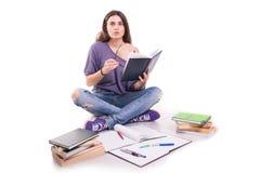 Ung stressad studentflicka som studerar högen av böcker arkivbilder