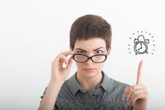 Ung strikt irriterad affärskvinna i exponeringsglas som pekar pekfingret upp på den utdragna ringklockan på den vita bakgrunden T arkivbilder