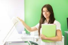 Ung student på en kopieringsmitt arkivfoton