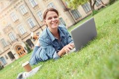 Ung student på universitetsområdet som ligger på gräs genom att använda bärbara datorn som ser den skämtsamma kameran fotografering för bildbyråer