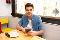 Ung student som använder hans smarta telefon för att läsa text, medan ha ett kaffe royaltyfria foton