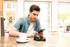 Ung student som använder hans smarta telefon för att läsa text, medan ha ett kaffe arkivbild