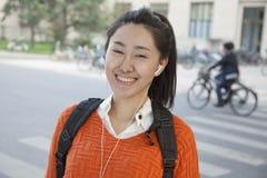 Ung student som lyssnar till musik, stående Royaltyfri Bild