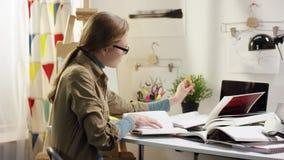 Ung student som på en gång läser tre böcker och skriver i anteckningsbok stock video