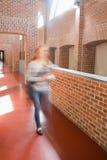 Ung student som rusar i de hållande mapparna för korridor Royaltyfri Bild