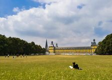 Ung student som vilar på gräsläsningen en bok royaltyfri fotografi