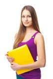 Ung studentflicka som rymmer den gula boken Royaltyfri Foto