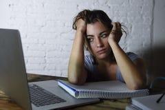 Ung studentflicka som studerar den trötta hemmastadda bärbar datordatoren som förbereder evakuerad och frustrerad känslaspänning  royaltyfri bild