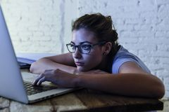 Ung studentflicka som studerar den trötta hemmastadda bärbar datordatoren som förbereder evakuerad och frustrerad känslaspänning  Arkivbilder